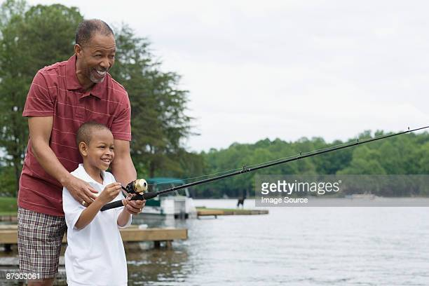 A grandfather teaching his grandson to fish