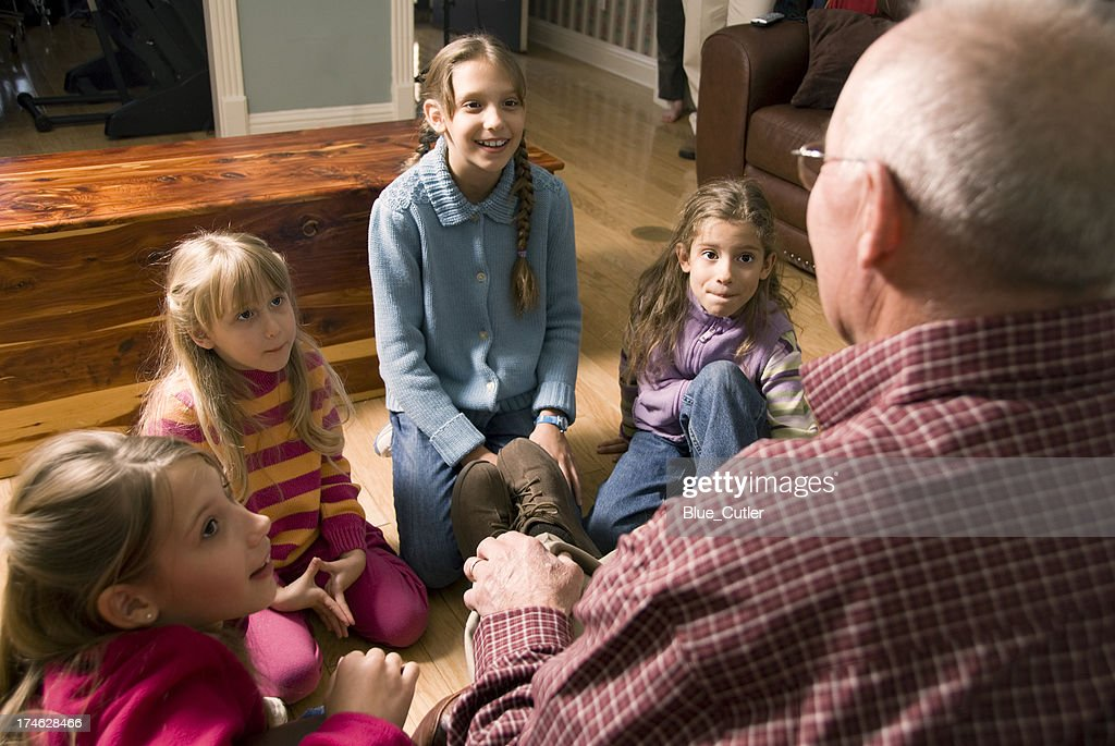 Grandfather telling a story to Grandchildren : Stock Photo