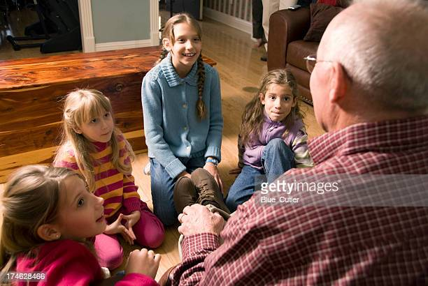 grandfather telling a story to grandchildren - fairytale stock pictures, royalty-free photos & images