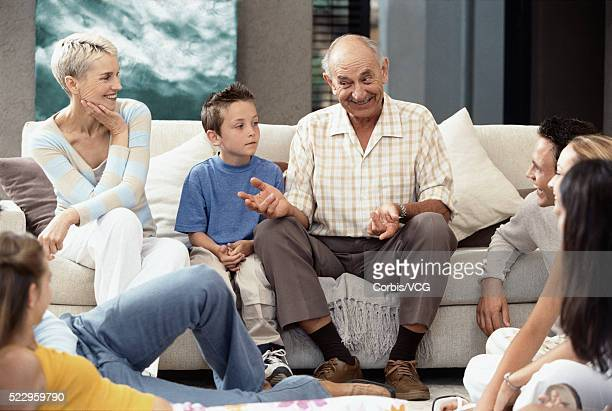 grandfather telling story to youngsters - storyteller stock pictures, royalty-free photos & images