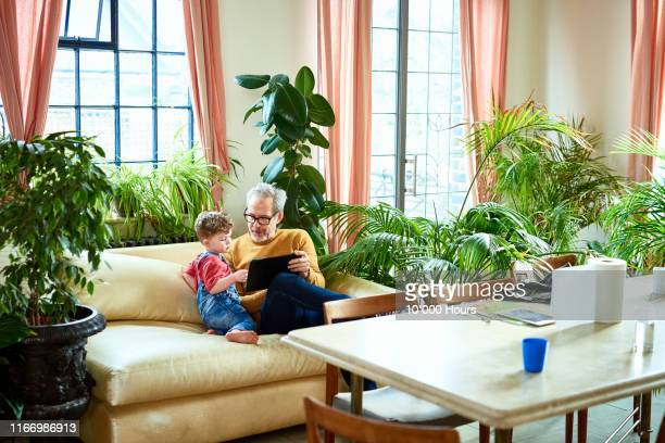 Grandfather using digital tablet with little boy