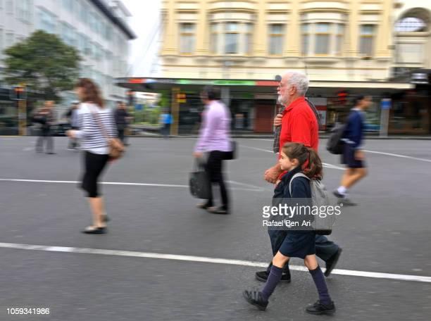grandfather walking his granddaughter to school - rafael ben ari stock-fotos und bilder