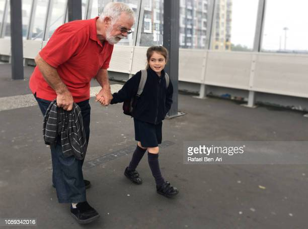 grandfather walking his granddaughter to school - rafael ben ari stockfoto's en -beelden