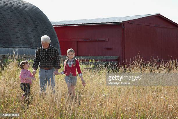Grandfather walking on farm with granddaughters
