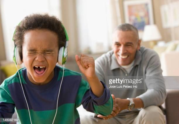 Grandfather watching grandson listening to music on headphones