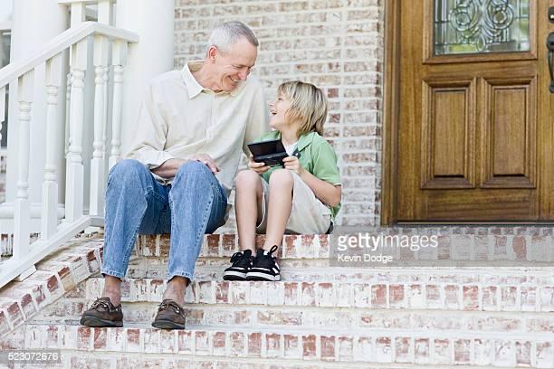 Grandfather watching grandson play handheld video games