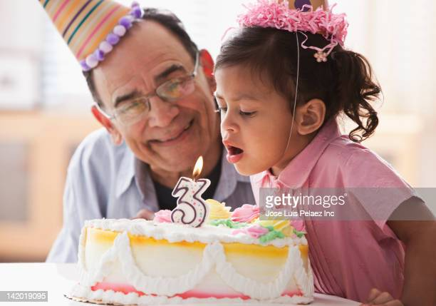 Grandfather watching Hispanic girl blow out candle on birthday cake
