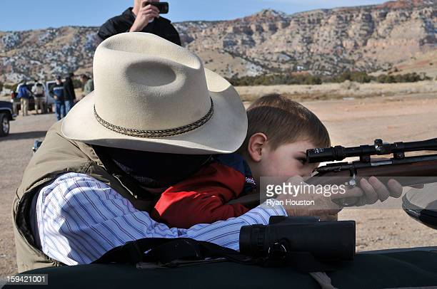 CONTENT] A grandfather wearing a cowboy hat is helping his grandson shoot a 22 rifle with a scope at the shooting range