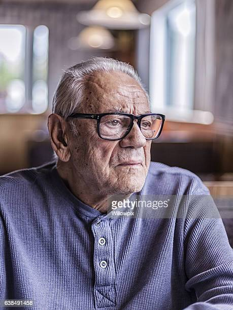 Grandfather Wearing Hearing Aid Listening To Family Discussion in Restaurant