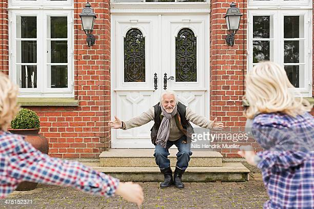 grandfather welcoming grandchildren with arms open - visit stock pictures, royalty-free photos & images