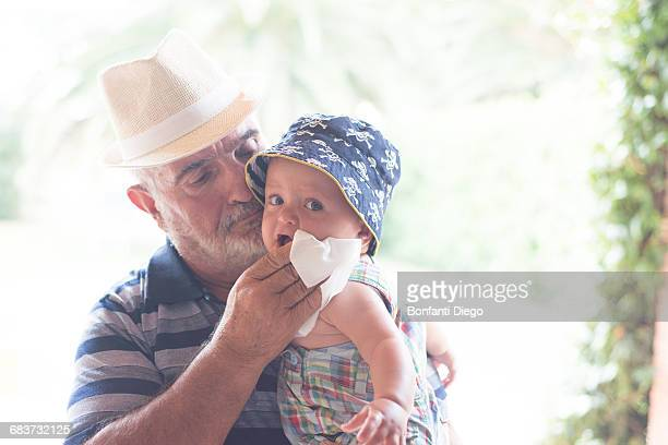 Grandfather wiping baby boys chin with handkerchief