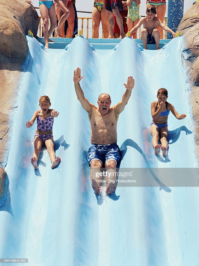 Grandfather with grandaughters (8-10) sliding down water ride : Stock Photo