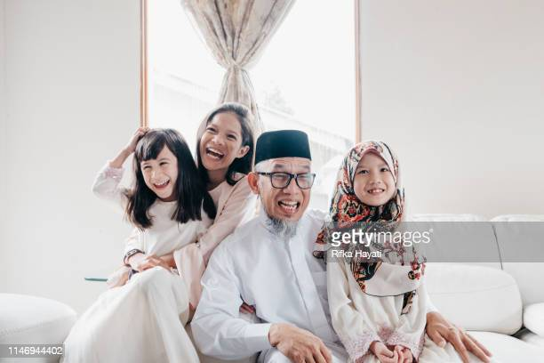 grandfather with grandchild during eid mubarak - malaysian culture stock pictures, royalty-free photos & images