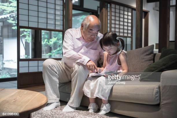 デジタル タブレットを使用してソファの上の孫娘と祖父
