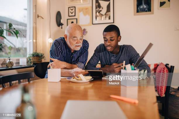grandfather with grandson doing research over digital tablet on table while sitting at home - disruptaging stock pictures, royalty-free photos & images