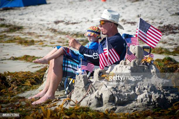 Grandfather with grandson next to a sand castle decorated with Stars and stripes at Pacific Beach watching the sea on Fourth of July