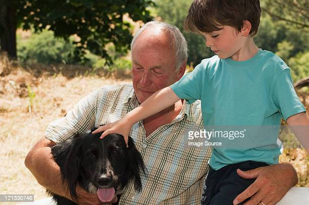 Grandfather with grandson patting dog