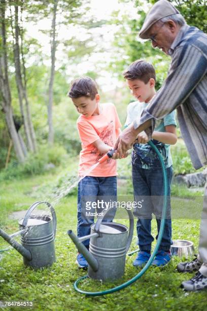 Grandfather with grandsons holding garden hose while filling watering cans in back yard