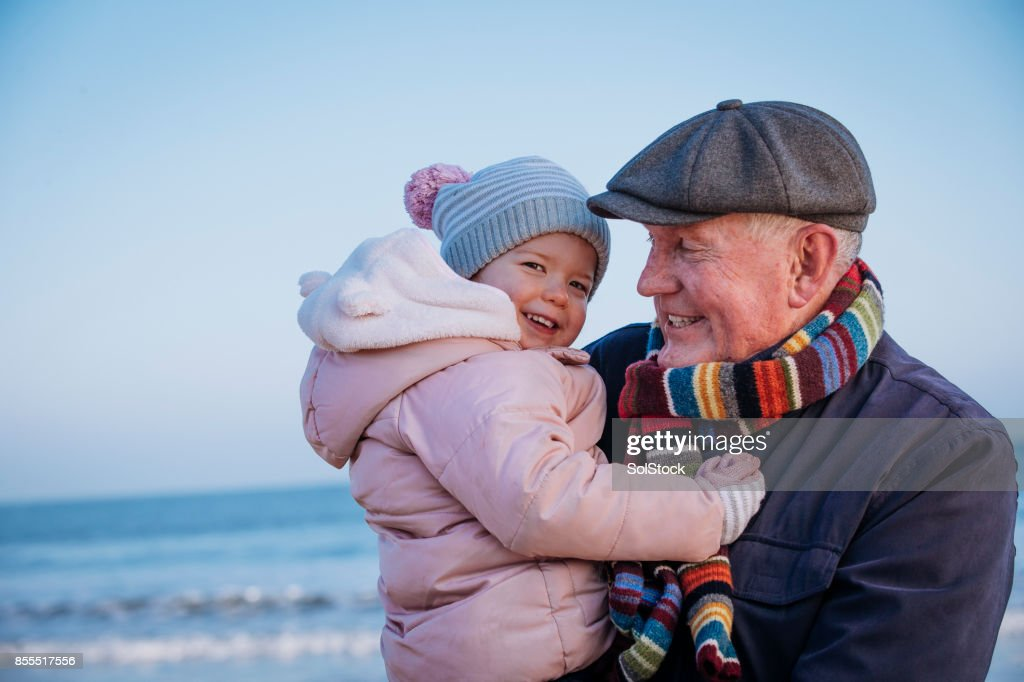 Grandfather with his Granddaughter on the Coast : Stock Photo
