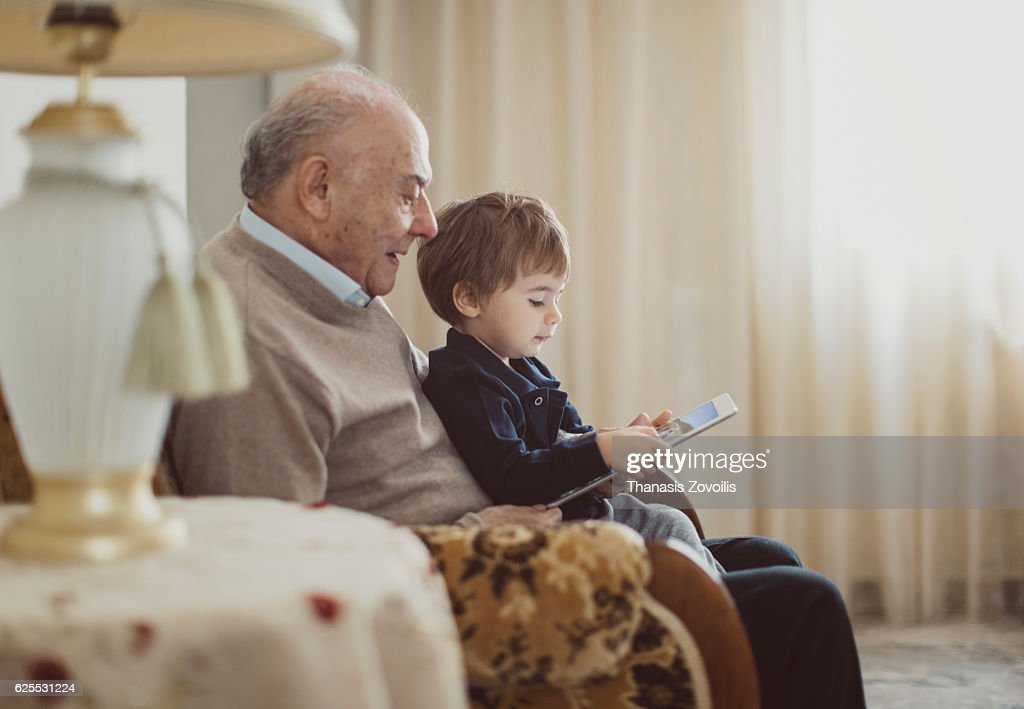 Grandfather with his grandson looking a digital tablet : Stock Photo