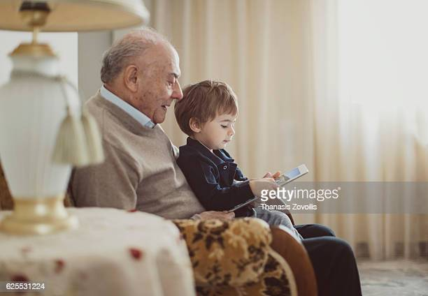 Grandfather with his grandson looking a digital tablet