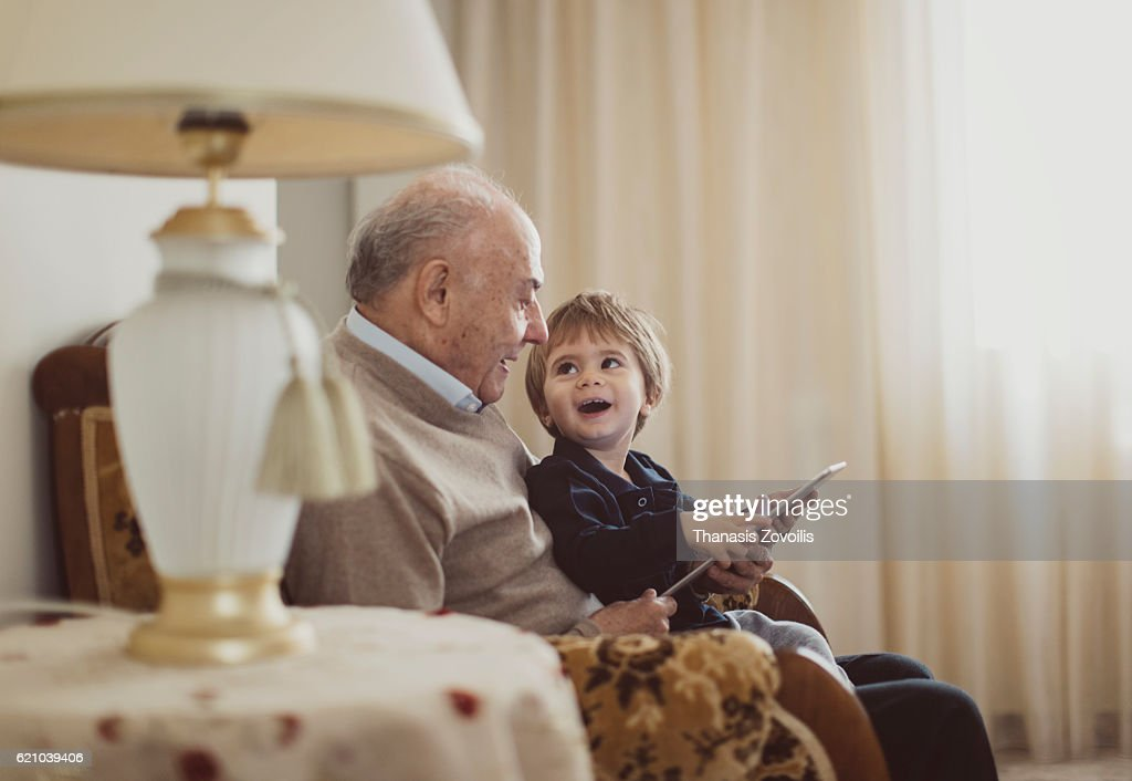 Grandfather with his grandson using a digital tablet : Foto de stock