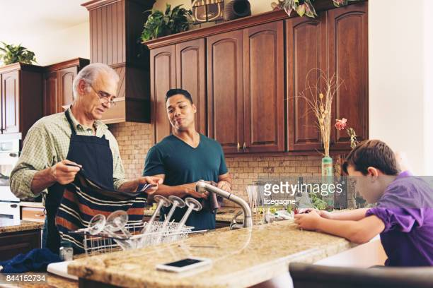 grandfather with his step-son and grand-son preparing thanksgiving dinner - happy thanksgiving text stock pictures, royalty-free photos & images