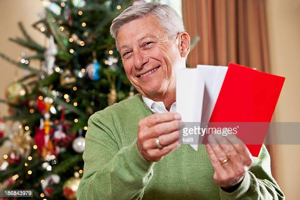Grandfather with holiday cards by Christmas tree