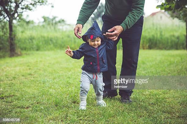 Grandfatherr helping boy to walk