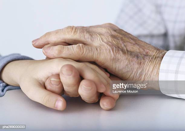 Grandfather's hands clasping girl's hand