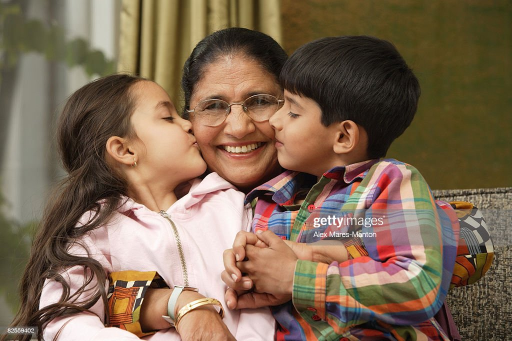 grandkids kiss grandmother cheeks : Stock Photo