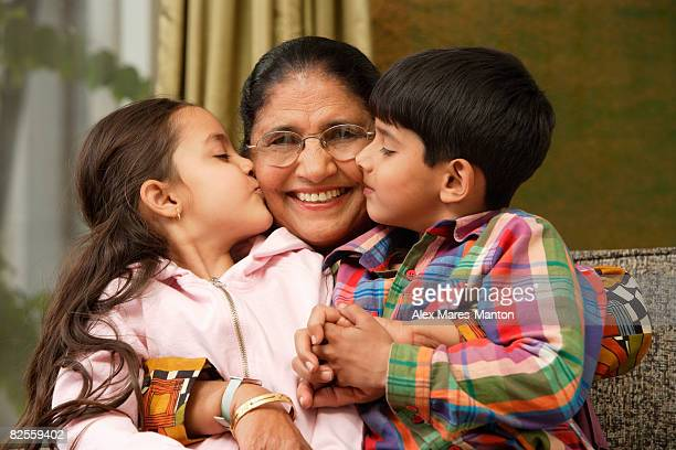 grandkids kiss grandmother cheeks - indian girl kissing stock photos and pictures