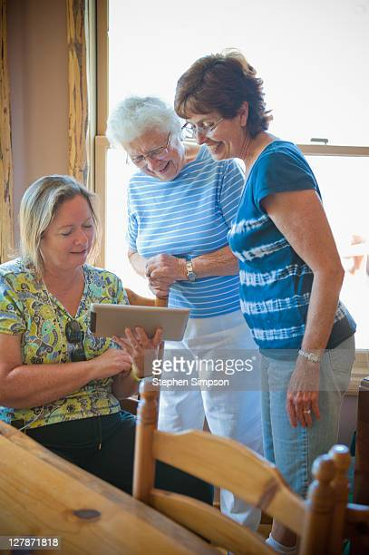 grandma and daughters sharing a tablet computer