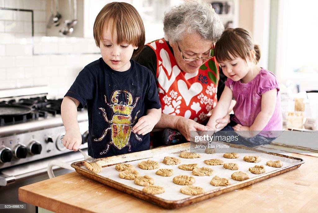 Grandma and grandchildren (3 yrs+2yrs) baking : Stock Photo