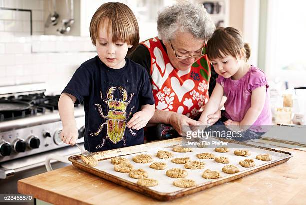 grandma and grandchildren (3 yrs+2yrs) baking - grandmother stock pictures, royalty-free photos & images