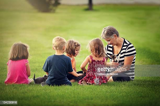 Grandma and grandchildren playing with kittens