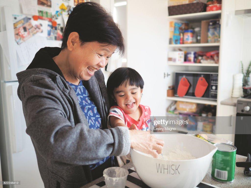 Grandma and grandson baking together : Stock Photo