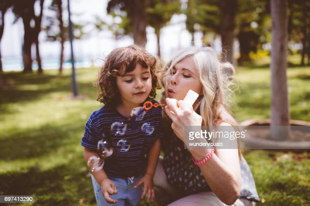 Grandma and grandson blowing bubbbles in a garden at summer
