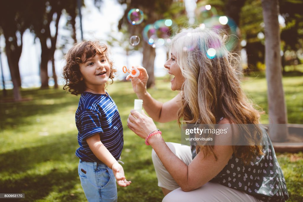 Grandma and grandson laughing and blowing bubbles at the park : Stock Photo