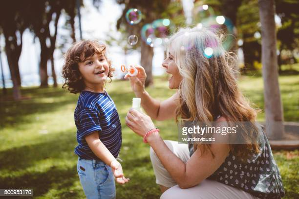 Grandma and grandson laughing and blowing bubbles at the park