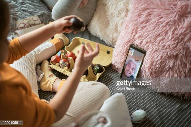oma und ihre enkelin binden sich zu ostern per videoanruf - ostern stock-fotos und bilder