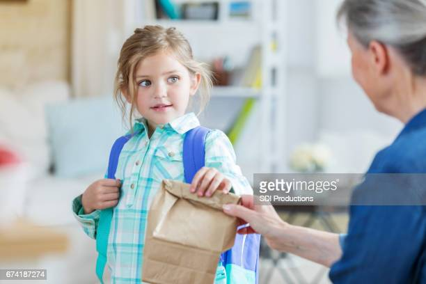 Grandma gives granddaughter a sack lunch