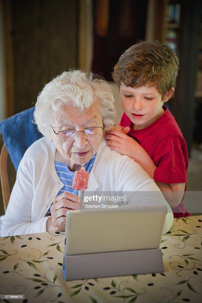 grandma & grandson exploring her tablet computer : Stock Photo