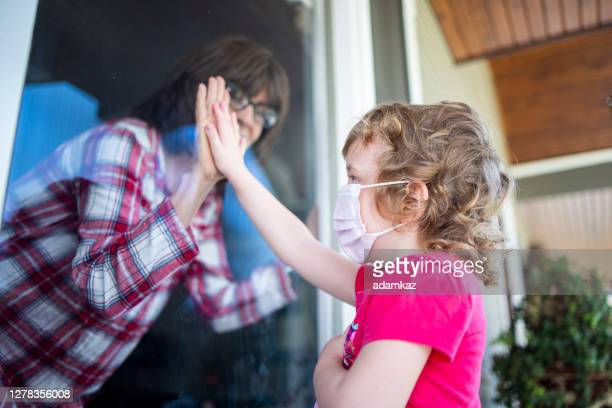grandma greeting granddaughter through window social distancing - visit stock pictures, royalty-free photos & images