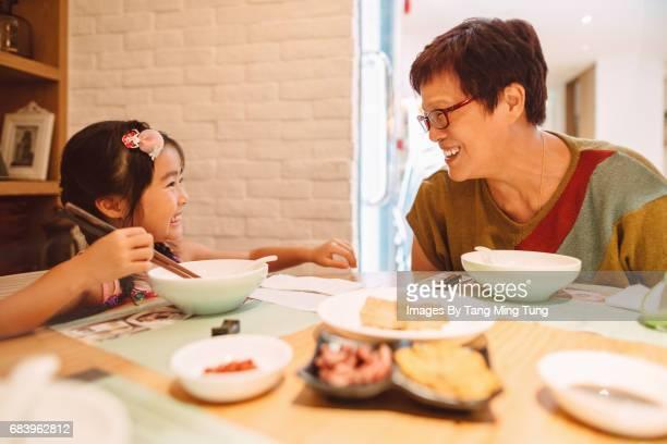Grandma having meal with lovely little granddaughter in a restaurant joyfully.