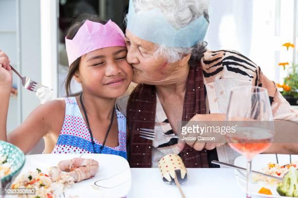 Grandma kisses granddaughter at Christmas lunch