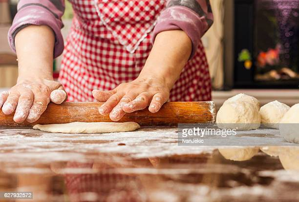 Grandma kneading and stretching the dough at home