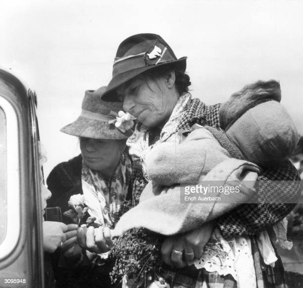 Grandma Mathers, her daughter Liza and granddaughter Betsy, three members of a gypsy family from Dunsfold in Surrey sell flowers to the spectators at...