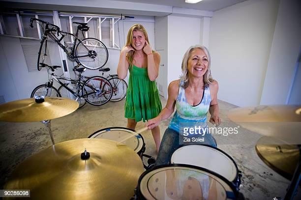 Grandma play drums with granddaughter behind her
