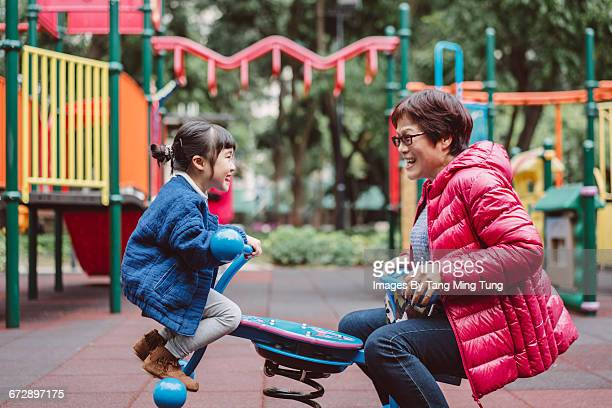 Grandma playing seesaw with granddaughter